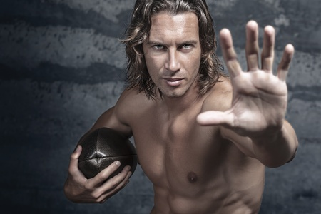 man with long hair: handsome bare chested muscle model is opening his hand in halt gesture and holds football ball Stock Photo