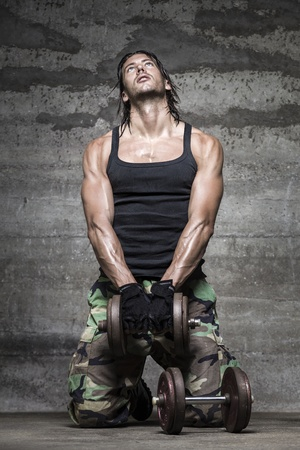 portrait of handsome athlete lifting weights on wall background photo