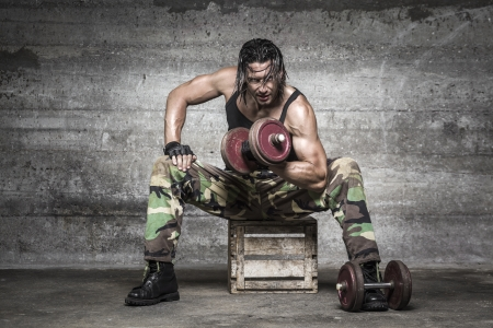 portrait of aggressive muscle man lifting weights on wall background Stock Photo