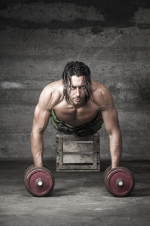 portrait of handsome long hair athlete pushing up with weights photo