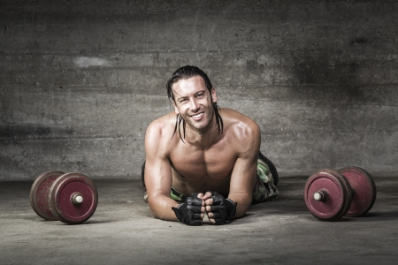portrait of muscle and smiling athlete lying on the floor photo