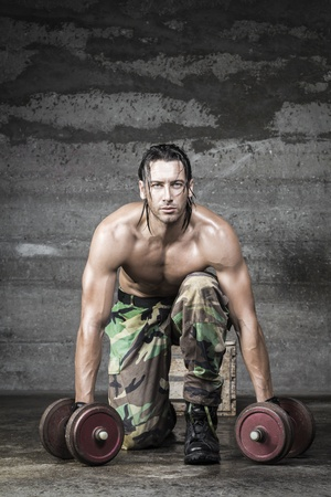 portrait of muscle athlete looking at camera and weightlifting photo