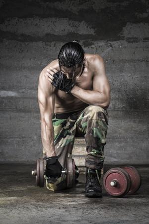 levantamiento de pesas: retrato de atleta muscular con pantalones de camuflaje pesas