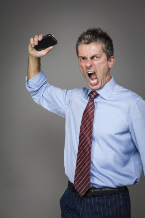 very angry businessman is throwing away his mobile phone photo