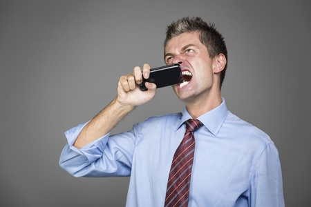 very angry businessman si biting his mobile phone photo