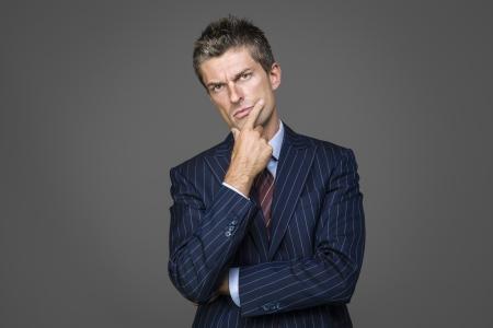 Portrait of suspicious elegant businessman looking in camera