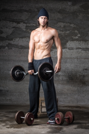 A handsome male with no shirt on lifting weights Stock Photo - 22220733