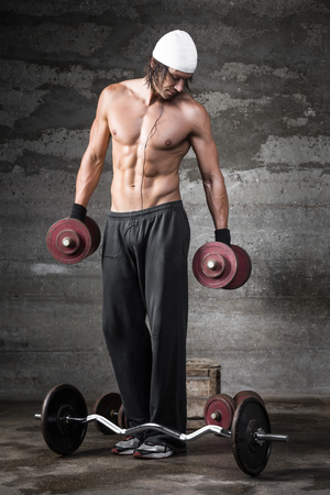 A good looking man lifting weights on dark background photo