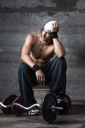 A portrait of pensitive muscular man during his rest from workout photo