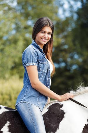 femme et cheval: portrait de la belle jeune femme assise cavalier sur son cheval à l'extérieur