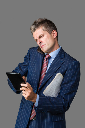 frowned: very busy businessman talking on his cellphone while using his tablet