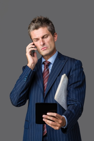 frowned: busy businessman talking on his smartphone while checking news on his tablet Stock Photo