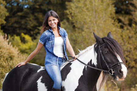 portrait of attractive brunette female rider sitting on her horse and smiling photo