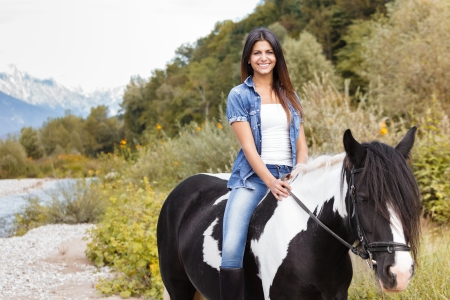 attractive brunette female rider sitting on her horse and smiling