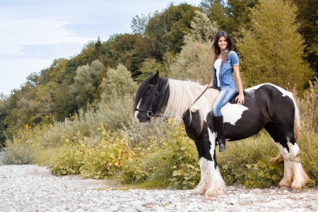bridle: beautiful young female sitting on her horse and looking at camera