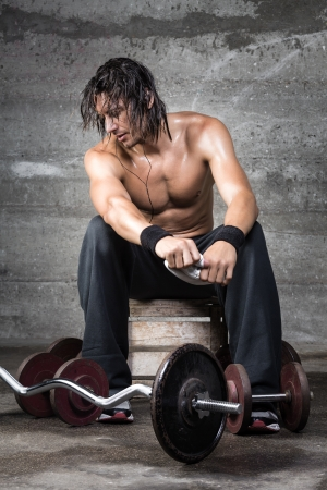 man with long hair: Portrait of sweaty bodybuilder after workout