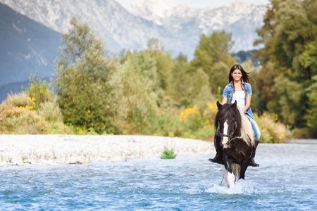 femme et cheval: Belle cavalier Femme traversant la rivière dans un paysage montagneux Banque d'images