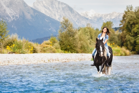 Smiling Female horse rider crossing river in a mountainous landscape photo