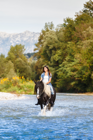 ady: Young Female horse rider crossing blue river in a mountainous landscape