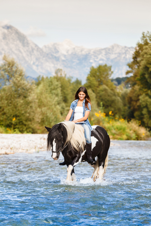 equitation: Beautiful Female sitting on horse while crossing river in a mountainous landscape
