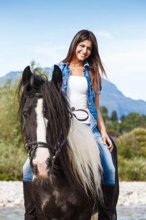 Young girl sitting on horse while crossing river in a mountainous landscape photo