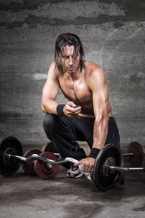 man with long hair: Portrait of Athlete fine tuning his music player