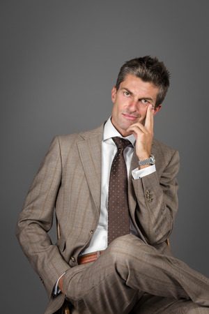 gray suit: Portrait of a classic elegant man on gray background Stock Photo