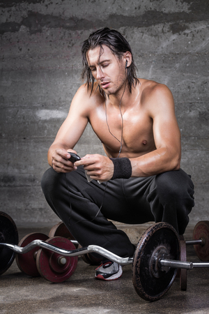 crouched: Portrait of handsome crouched athlete checking his music player while having a rest from workout