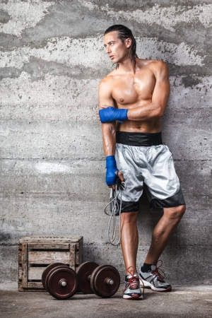 Portrait of attractive boxer man standing on the wall and looking aside photo