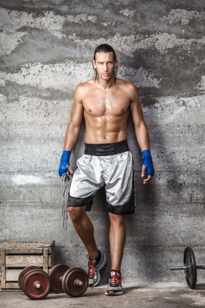 Portrait of handsome boxer man standing on the wall and looking at camera with intense gaze photo