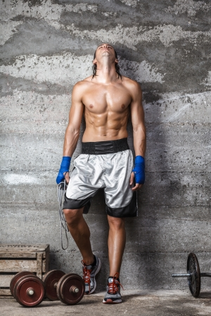 Portrait of muscular boxer man standing on the wall and looking up