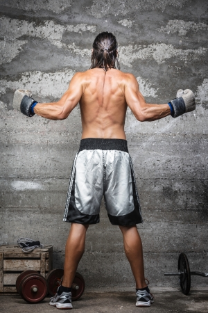 Rear view of muscular boxer man standing on the wall  photo