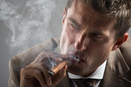 gaze: Bijgesneden portret van harde blik zakenman terwijl het roken van een Cubaanse sigaar