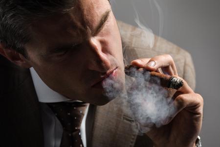 smoking a cigar: Elegant businessman smoking a cuba cigar Stock Photo