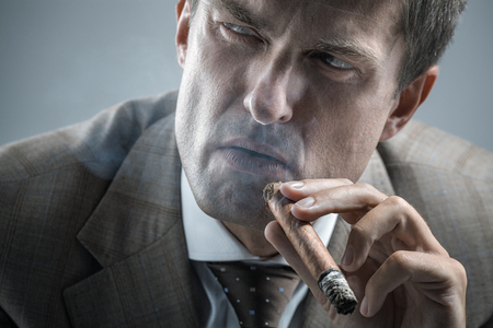 sever: Elegant adult man smoking a cigar while looking aside with sever gaze
