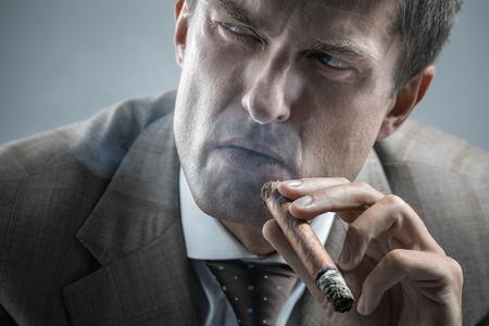 hombre fumando puro: Hombre adulto elegante fumar un cigarro mientras mira a un lado con la mirada severa