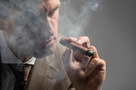 Cropped portrait of a serious elegant man smoking a cigar photo
