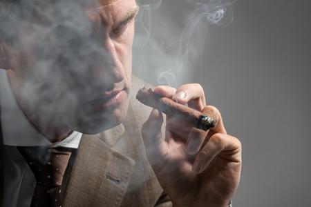 smoking cigar: Cropped portrait of a serious elegant man smoking a cigar Stock Photo