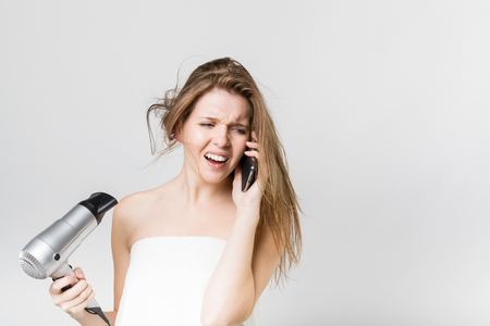 Portrait of a beautiful young girl blow drying her hair while talking on the smartphone photo