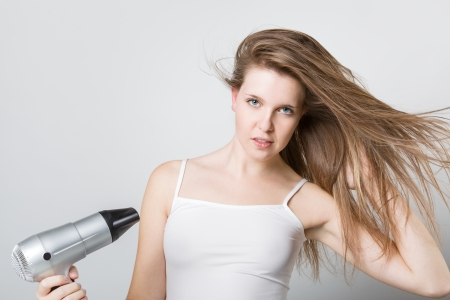 Portrait of a attractive young girl blow drying her hair and looking at camera photo