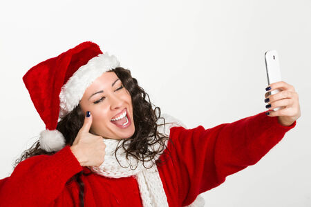 Attractive brunette santa girl taking self portrait with a smartphone in ok gesture photo