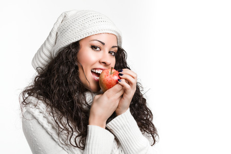 trendy young brunette woman biting an apple and smiling photo