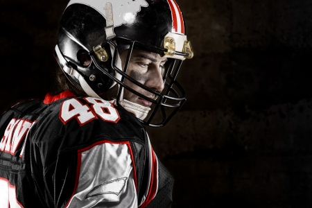 Portrait of thoughtful american football player on dark background