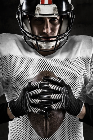 dark face: Portrait of american football player holding a ball and looking at camera  Stock Photo
