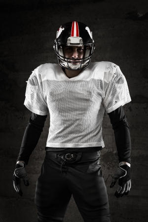 man face: Portret van american football speler op zoek naar de camera op een donkere achtergrond Stockfoto