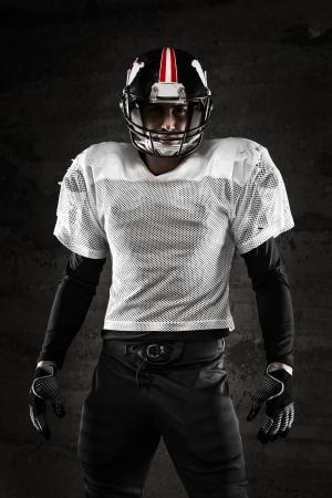 handsome men: Ritratto del giocatore di football americano guardando la telecamera su sfondo scuro