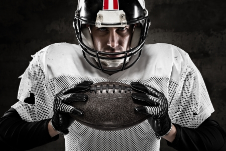 closeup: Portrait of american football player holding a ball and looking at camera  Stock Photo