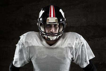american football player: Portrait of american football player looking at camera on concrete background