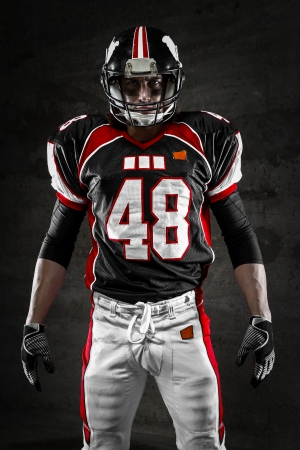 Portrait of american football player looking at camera on dark background Foto de archivo