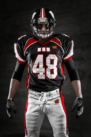 uniforme de futbol: Retrato del jugador de fútbol americano que mira la cámara sobre un fondo oscuro